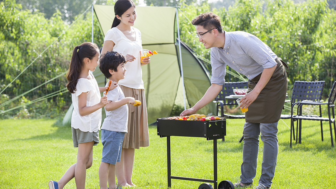 Young family barbecuing outdoors